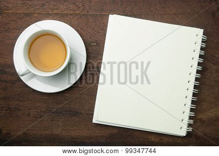 cup of tea and note book on wooden background.