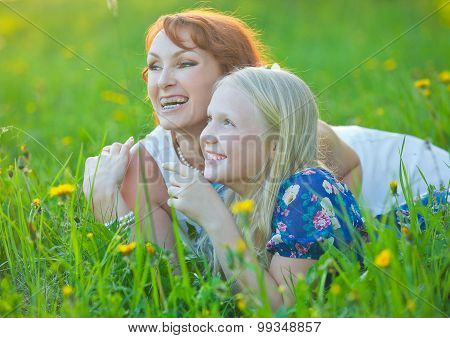 Mom with braces and her little daughter lie on grass smiling at the park