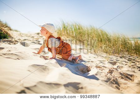 Little cute toddler boy climbing up on a sandy hill on the beach