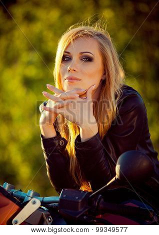 Young sexy woman sitting on a motorcycle