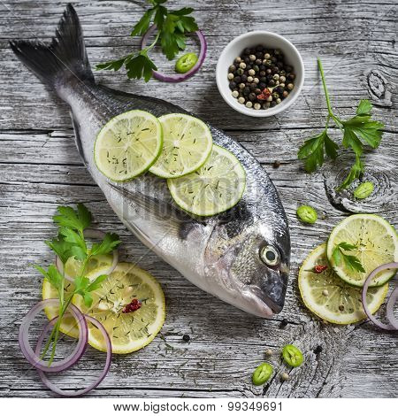 Fresh Dorado Fish, Lemon, Lime And Parsley On A Light Wooden Surface