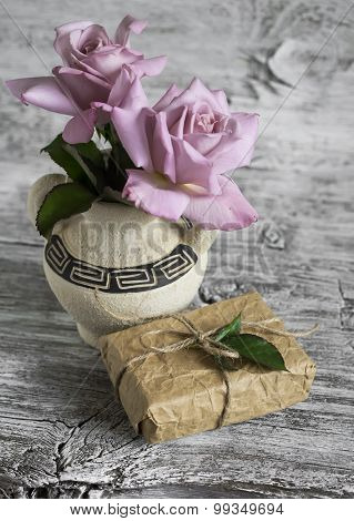 Pink Roses In A Ceramic Vase With Greek Ornament, Homemade Gift Box On A White Wooden Surface, Vinta