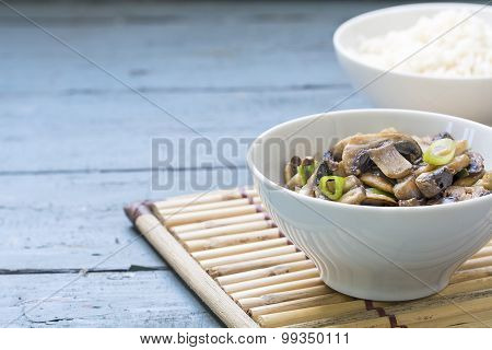 Mushroom Vegetable Dish And Cooked Rice In White Bowls On A Bamboo Mat And Blue Wood