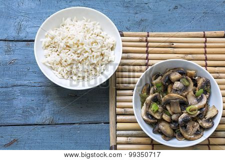 Mushroom Vegetables And Cooked Rice In Bowls On A Bamboo Mat And Rustic Blue Wood
