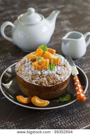 Simple Pound Cake, Decorated With Icing Sugar And Apricots On A Brown Plate On A Dark Wooden Backgro
