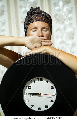 Woman With Big Clock Sitting In The Room.