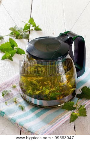Teapot Of Herbal Tea With Fresh Mint Flower On A Wooden Table