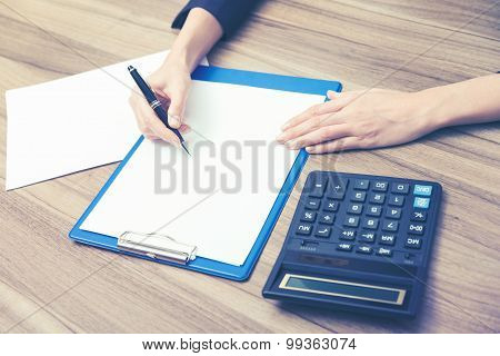 Closeup Of A Business Woman's Hands While Writing Down Some Essential Quantitative Information. Calc