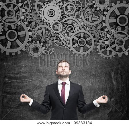 Meditative Businessman Is Thinking About The Project Optimisation. Gears As A Concept Of Thought Wor