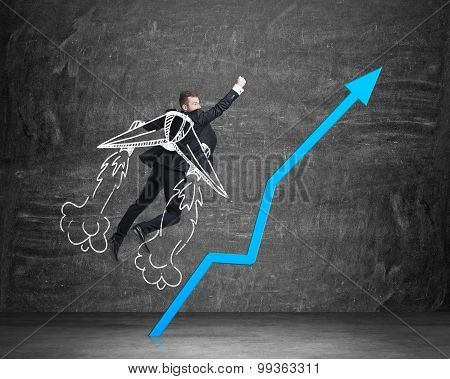Businessman Is Taking Of To The Success With Drawn Wings. Rocketing Blue Arrow. Black Chalkboard On