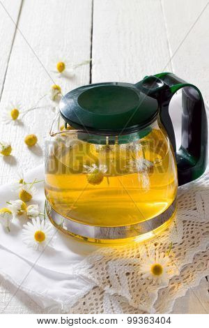 Teapot Of Herbal Tea With Chamomile Flowers On The Wooden Table
