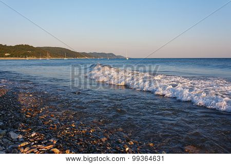 Tranquil waves on the beach against the backdrop of mountainous coast