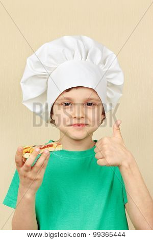 Little funny chef is tasting cooked pizza