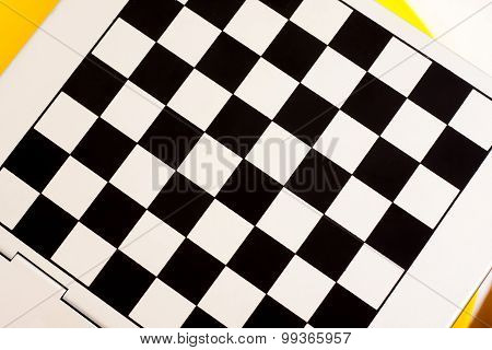 Metallic chess board on a yellow white backgound