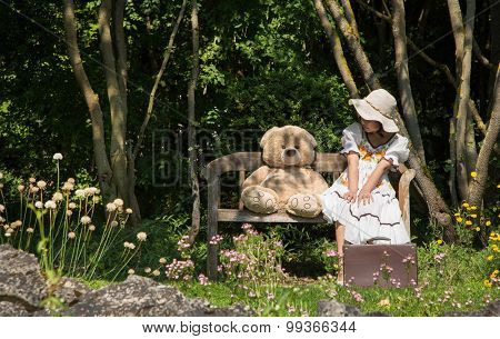 Little cute girl with her teddy bear sitting on a wooden bench in the garden talking together.