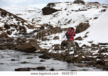 Active adventurous hiking man trekking by the river, cold winter landscape snowy icy wilderness