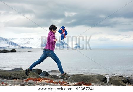 Independent asian woman traveling in iceland, having fun jumping on rocks by the ocean enjoying the beautiful rugged icelandic landscape