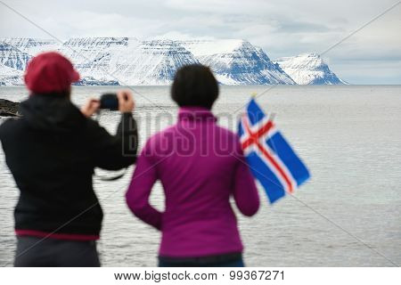 Girlfriends traveling together enjoying the scenery taking photos from the viewpoint in the westfjords, iceland. independent self drive holidays