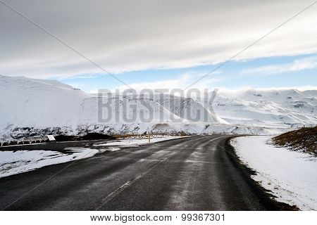 On the road along empty icelandic road with beautiful winter snowy mountains landscapes