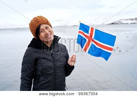 Young asian woman traveler happy in beautiful iceland viewpoint  waving flag carefree holiday vacation