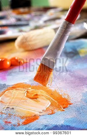 Professional acrylics orange paint on canvas and loaded brush