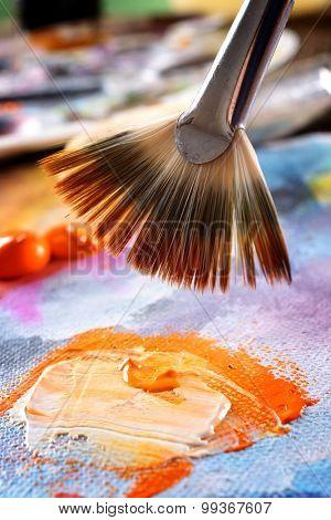 Professional acrylics orange paint on canvas and brush