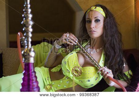 Beautiful Brunette Belly Dancer Wearing Bright Green Comtume, Resting With Hookah. Indoor.