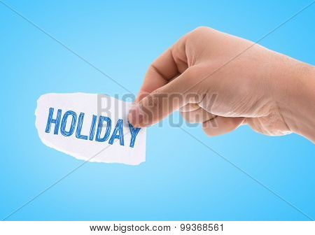 Piece of paper with the word Holiday with blue background