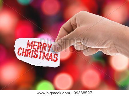 Piece of paper with the word Merry Christmas with bokeh background