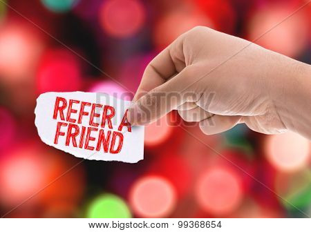 Piece of paper with the word Refer a Friend with bokeh background