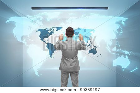 business, people, technology and global communication concept - businessman working with hologram of world map from back over gray room background