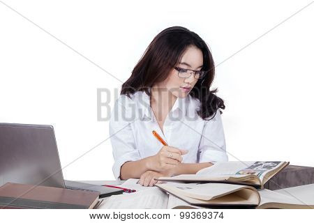 Student Reads Literature Book While Writing