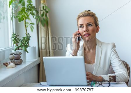 Attractive business woman in the home office working on laptop and speaks on a mobile phone. Conversation with the client. Modern business woman.