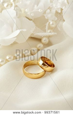two wedding rings, pearls and flowers