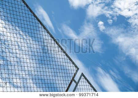 steel net fence against blue sky