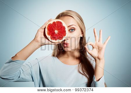 Young Blonde Woman With Grapefruit In Her Hands Studio Portrait Isolated On Blue Background. Young B