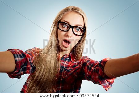 Close Up Portrait Of A Young Surprised Blonde Girl Holding A Smartphone Digital Camera With Her Hand