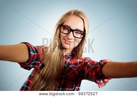 Close Up Portrait Of A Young Flirting Blonde Girl Holding A Smartphone Digital Camera With Her Hands