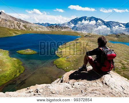 Trekker takes a rest looking at mountain panorama. Male, caucasian, sitted on a rock, summer sunny day. Gran Paradiso National Park, Western italian Alps, Italy, Europe.
