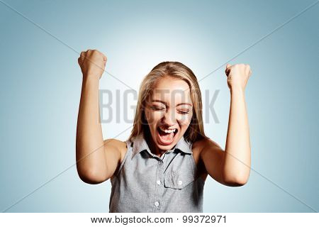 Pretty Young Blonde Woman Throwing Her Arms Up Into The Air And Laughing In Jubilation At Her Succes