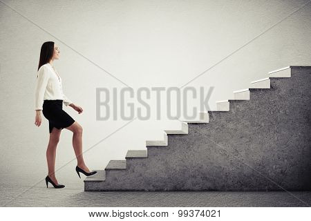 successful businesswoman in formal wear walking up concrete stairs over light grey background