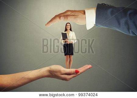 big female palm holding small happy businessman with black folder and big male hand covering her over grey background