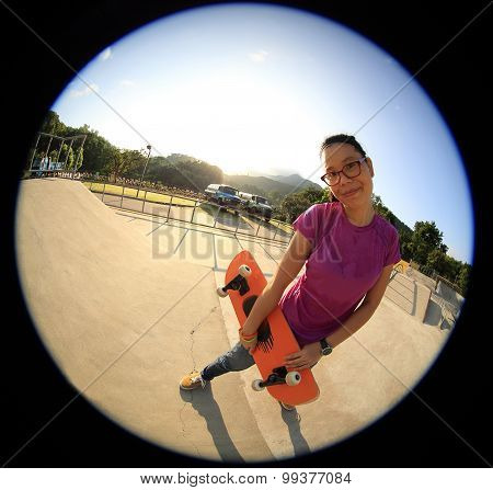 young woman skateboarder with skateboard at skatepark