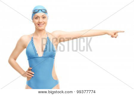 Female swimmer in a blue swimming costume pointing with her hand isolated on white background