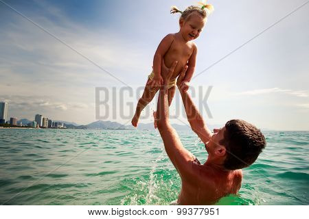 Father Tosses Up Smiling Little Daughter Above Sea Water