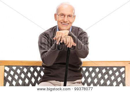Calm senior gentleman with a cane sitting on a bench and looking at the camera isolated on white background