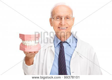 Mature dentist in a white coat holding a denture and looking at the camera isolated on white background