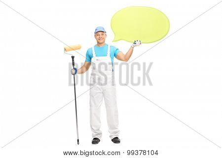 Young male house painter in a white jumpsuit holding a paint roller and a big yellow speech bubble isolated on white background