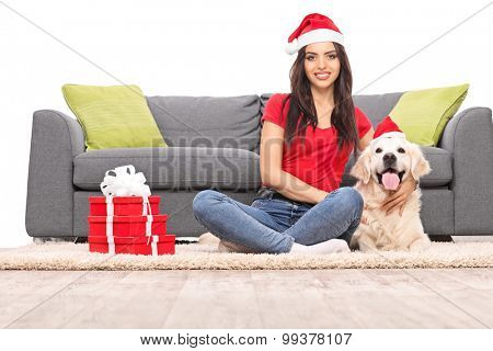 Young girl with Santa hat sitting in front of a gray sofa with her dog isolated on white background