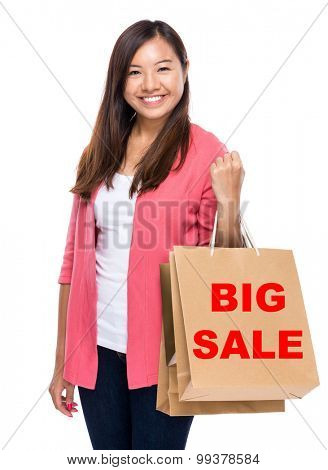 Happy woman with shopping bag and showing big sale